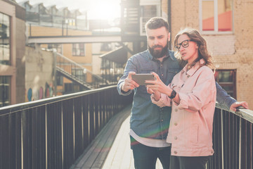 Young bearded man and woman stand outside and discuss what they see on smartphone screen. Girl shows the guy information