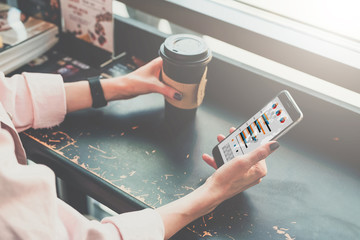 Close-up of a smartphone and a cup of coffee in the hands of a hipster girl sitting in a cafe at a black table.