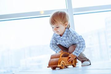 Boy rolls a toy car