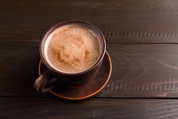 Hot chocolate or cocoa drink in clay cup, on dark brown wooden table