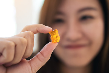 Closeup image of a beautiful Asian woman smiling , holding and looking at orange gummy bear