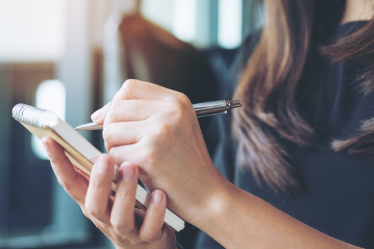 Closeup image of a woman writing and taking note on notebook in office