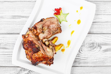 Roasted pork stuffed with mushrooms, peach, carambola, cranberries and sweet sauce on plate on wooden background close up