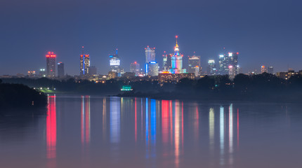 Fototapete - Colorful night panorama of Warsaw skyline, Poland, over Vistula river in the night