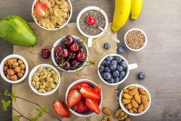 Ingredients for a healthy breakfast, nuts, oatmeal, honey, berries, fruits, blueberry, orange, pomegranate seeds, almonds, walnuts The concept of natural organic food in season Top view
