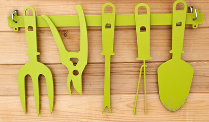 gardening tools cut out of metal and mounted on wooden background