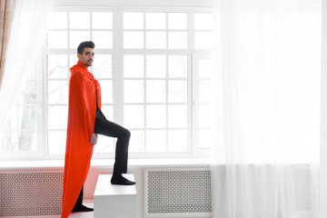 Businessman in red superhero cloak. Young man in suit and superman cape on stairs