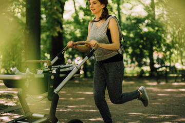 Young beautiful sporty mother jogging and pushing baby stroller in sunny summer day.