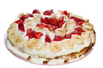 Sponge cake homemade with condensed milk decorated with banana slices and strawberries isolated on white background