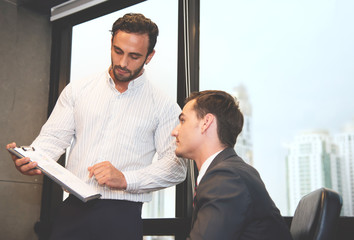 Business people discussing with chart graph documents at office on skyscraper background.