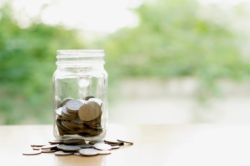Savings word with money coin in glass jar.financial concept