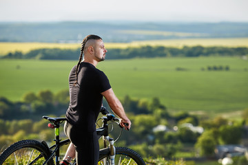 Close-up portrait of the mountain biker looking at beautiful landscape.