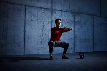 Dark picture of athlete doing squats