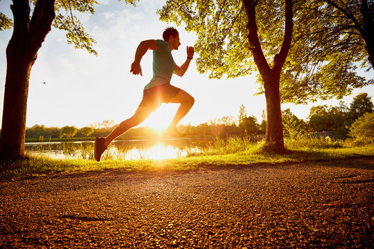 man running fast in park during sunset