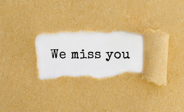 Text We miss you appearing behind ripped brown paper