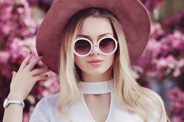 Wall Mural - Outdoor close up portrait of young beautiful happy girl posing in street, near blooming tree. Model wearing stylish round sunglasses, pink hat, wrist watch, white trendy shirt. Female fashion concept