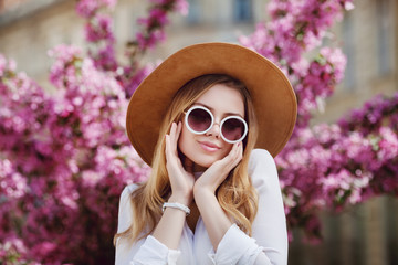 Wall Mural - Outdoor close up portrait of young beautiful happy girl posing in street, near blooming tree. Model wearing stylish round sunglasses, yellow hat, wrist watch, white shirt. Female fashion concept