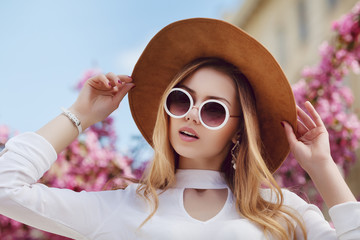 Wall Mural - Outdoor close up portrait of young beautiful woman wearing stylish round sunglasses, yellow hat, white shirt. Model looking at camera, posing in street, near blooming flowers. Female fashion concept