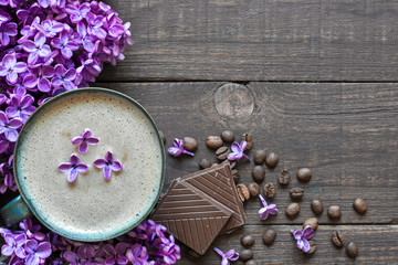 morning cup of coffee with purple lilac flowers and chocolate