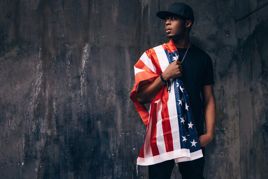 Afro american guy with US flag on dark background. Patriot, national event celebration, independence day, immigration, usa citizen concept
