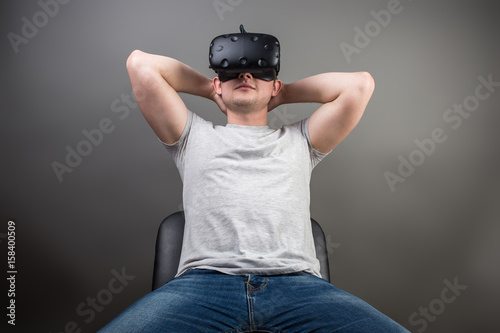 f9e0a072c64 sitting man wearing virtual reality goggles. Smartphone using with VR  headset. Horizontal