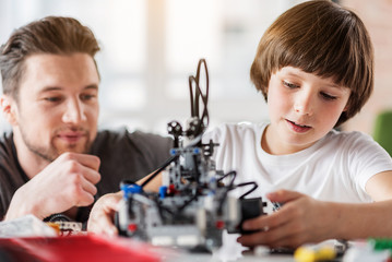 Interested serious male kid holding spare part