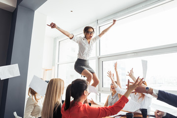 picture of happy business team celebrating victory in office. woman stand on table