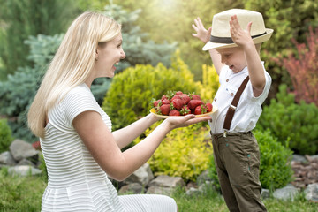 A young mother treats her baby son ripe fragrant strawberries.