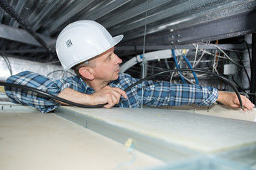 Electrician installing cables into confined space