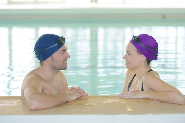 Male and female swimmers chatting at side of pool