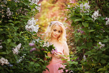 Beautiful woman enjoying lilac garden, young woman with flowers in green park. cheerful teenager walking outdoor. soft light style color.Young girl in beautiful wreath of lilac flowers