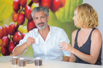 Man and woman sampling coffee