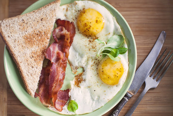 American breakfast with sunny side up eggs, bacon, toast, coffee, green salad, wood background. Top view