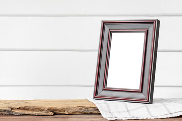 Picture frame put on wooden table in white wood wall room.