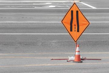 Traffic lanes merging sign and warning cone. Diamond shape transportaton symbol. Gray asphalt, striped lines..