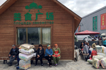 "People sit under a sign which reads ""good food plaza"" on the Chinese side of the China-Kazakhstan Horgos International Border Cooperation Center (ICBC), in Horgos"