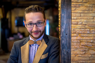 Portrait of a stylish man with a beard in glasses with a wooden bow tie
