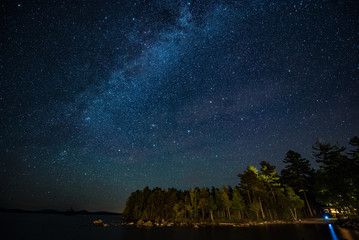 Maine- Milkyway shining in the night sky over trees