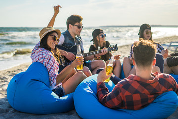 group of friends drinking on the beach party - Young hipster man playing on guitar near the sea and other people dancing and listening to music