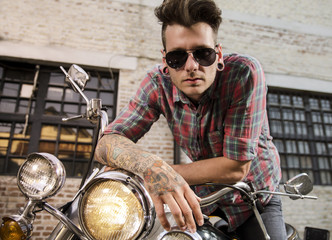 Portrait of handsome tattooed young man with sunglasses on vintage motorcycle
