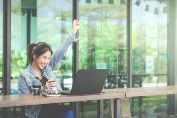 Cute beautiful Asian girl celebrate with laptop, success or happy pose, education or technology or startup business concept, in coffee shop workplace with copy space.