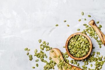 Raw pumpkin seeds, food background, top view