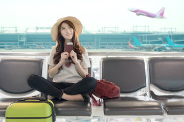 Cute asian student college traveler feeling happy action with travel plan and waiting for flight at airport terminal. Teenager travel concept.