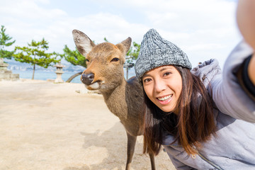 Woman taking selfie with Deer in Hiroshima