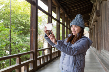Woman taking photo in japanese architecture