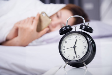 clock with woman using her smartphone on bed