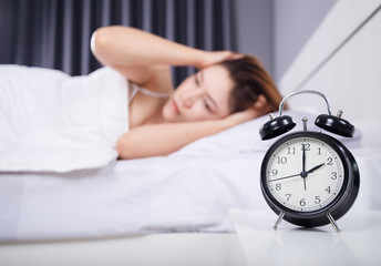 clock with woman sleepless on bed