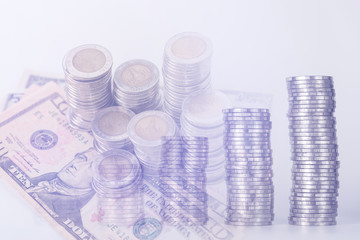 Double exposure of piles of coins dollar currency and account book with calculator on white background