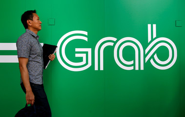 A man passes a Grab sign at their office in Singapore