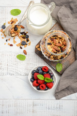 Homemade granola with fresh berries on white wooden background, top view, copy space